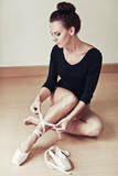 Ballet dancer tying slippers around her ankle woman ballerina po