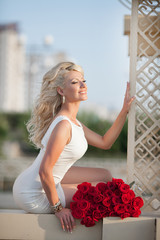 Beautiful happy woman with roses flowers outdoor