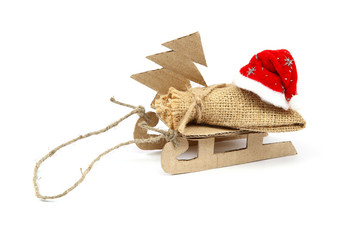 Sledge with sackcloth bag, Christmas tree and Santa Claus hat.