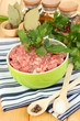 Bowl of raw ground meat with spices on wooden table