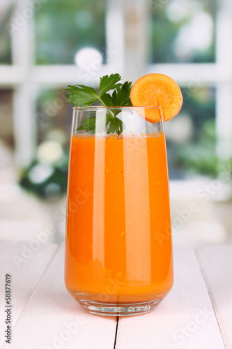 Glass of carrot juice on wooden table, on window background