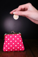 Pink purse and coin in female hand on table on black background