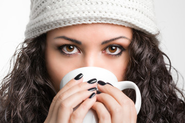Beautiful brunette drinking from a mug on white background
