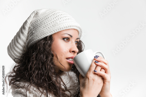Closeup of a pensive young brunette drinking from a mug and remi