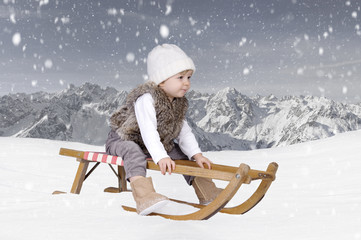 Little toddler outdoors in the snow in the alps