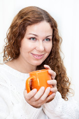 Smiling young woman with orange tea cup in hands