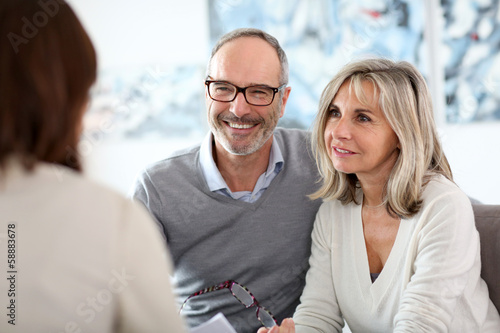 Leinwanddruck Bild Senior couple meeting financial adviser for investment