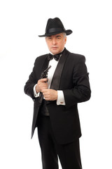 The elegant man in a tuxedo with a hat and a revolver