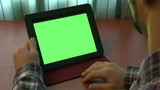 Man using digital tablet with a green screen