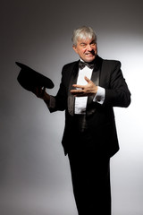 Elegant man in tuxedo and hat on a gray background.