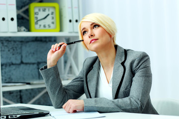 Beautiful pensive businesswoman sitting at the table in office