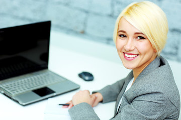 Happy businesswoman sitting at her workplace