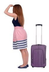 back view of young beautiful redhead woman traveling with suitca