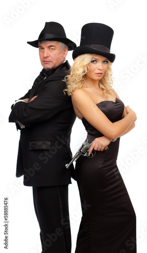 Man and woman in elegant suits and hats with a revolver.