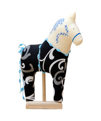Hand made soft toy horse isolated on black with blue on the stan
