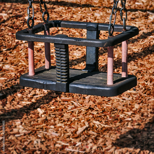 Toddler swing empty in the playground square composition