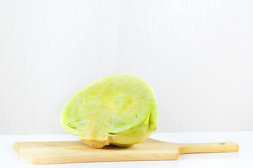 Half of fresh raw cabbage on a cutting board closeup