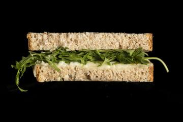 Sándwich de queso y rúcula, sobre fondo negro