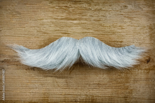 Fake mustache on an old wooden background