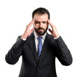 Young businessman with headache over white background