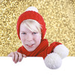 Junge mit roter Pudelmütze  schaut über weiße Wand