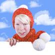 Junge mit roter verschneiter Pudelmütze  schaut über weiße Wand