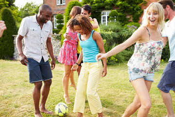 Group Of Friends Playing Football In Garden