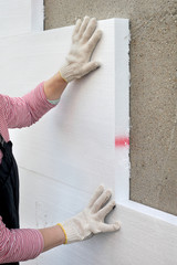 Home renovation worker placing styrofoam insulation to wall