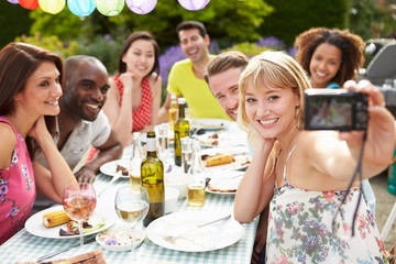 Friends Taking Self Portrait On Camera At Outdoor Barbeque