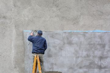 Worker spreading mortar with trowel to styrofoam insulation
