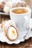 Cannolo siciliano pastry dessert with a cup of espresso coffee