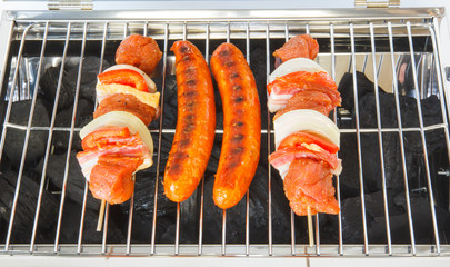 Sausages and meat skewers on the barbecue