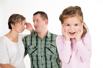 Sich freuendes Kind, genervte Eltern im Hintergrund