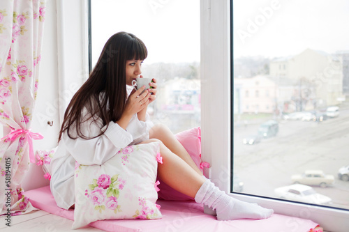 Pretty young woman drinking morning coffee