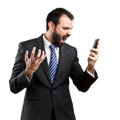 Young businessmen shouting to mobile over isolated background.