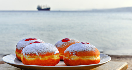 Festive donuts with jam on background of the Red Sea