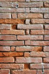 Muro irregolare di vecchi mattoni rossi vertilale