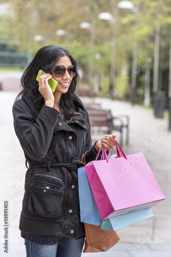 Woman talking by phone and holding shopping bags.