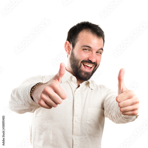 Young man with thumbs up over white background