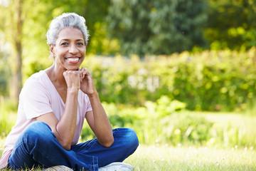 Attractive Mature Woman Sitting In Garden