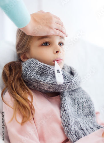 ill girl child with thermometer and caring mother