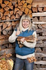 Glückliche Frau holt Holzscheite zum Heizen