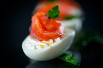 boiled egg with salty salmon on black background