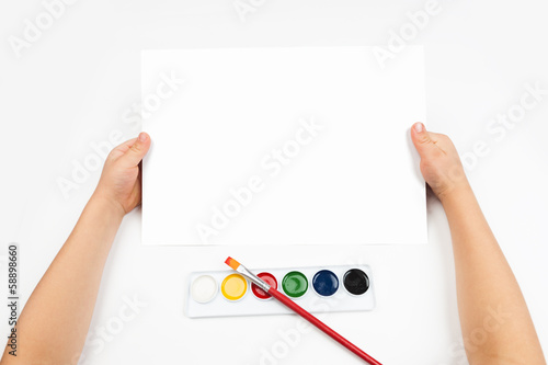 Blank sheet in child hand and watercolor paint