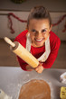 Portrait of smiling young housewife rolling pin