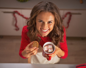 Portrait of smiling young woman enjoying christmas cookies