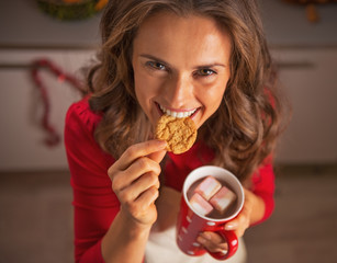 Smiling young housewife eating christmas cookies in kitchen