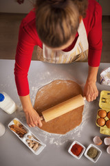 Young housewife rolling pin dough in kitchen
