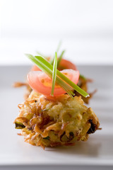 fried potato rostis topped with tomato and scallion.