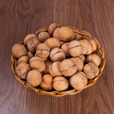 walnuts in a wicker basket on a wooden background